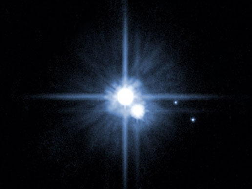 An image of Pluto and its moons taken by the Hubble  telescope.