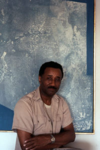 "Murray in front of ""With Blue"" by Romare Bearden (1962), which hung above the Murrays' dining table for decades. © The Albert Murray Trust."