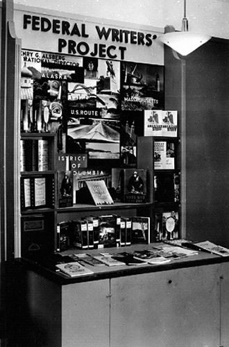 Federal Writers' Project desk with posters and books behind it.