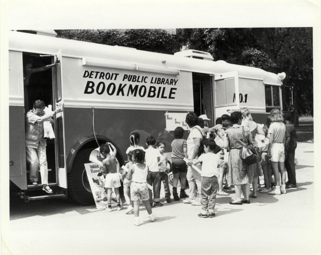Children wait in line outside the Detroit Public Library bookmobile.