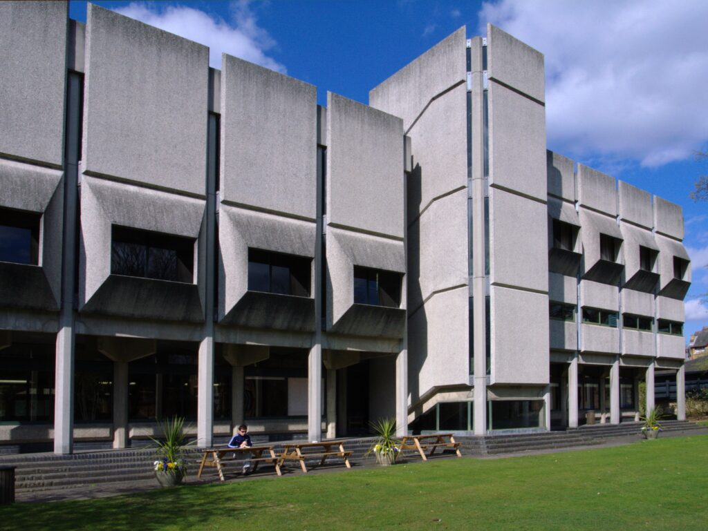 """""""The Besse Building"""" by Steve Cadman; gray brutalist building with square panels and columns overlooking green lawn."""