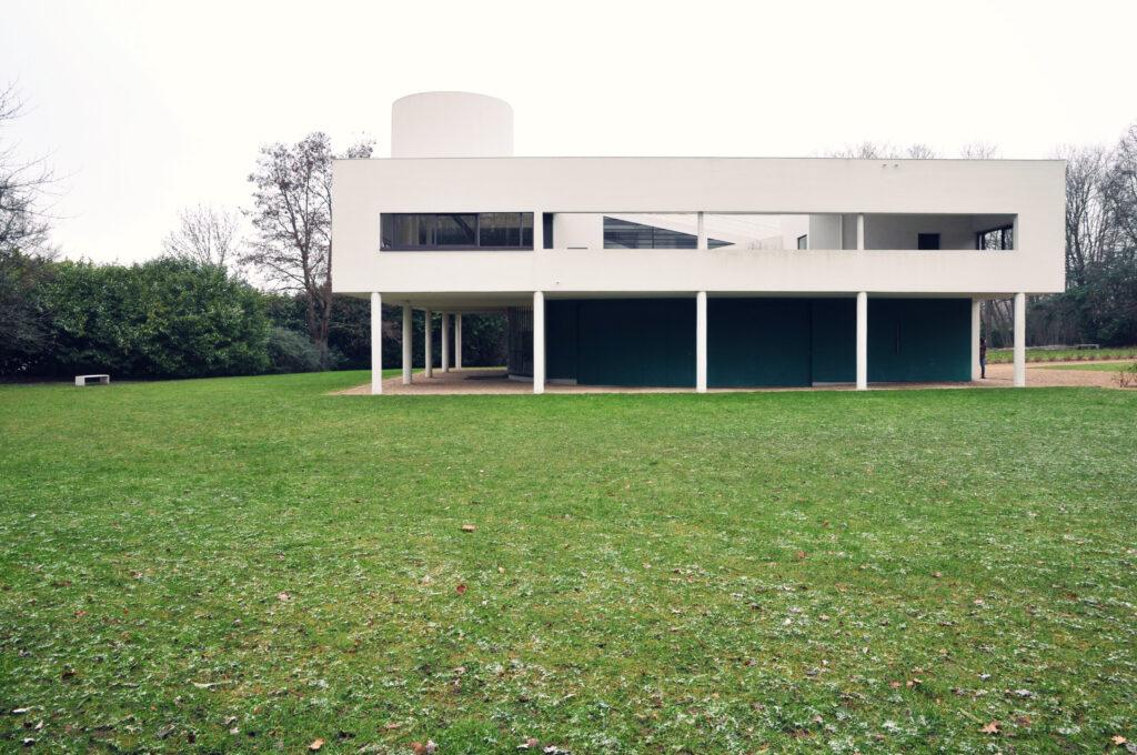 """La Villa Savoye"" by M-Louis®. White rectangular building with long skinny stilt-like columns overlooking a vast green lawn."