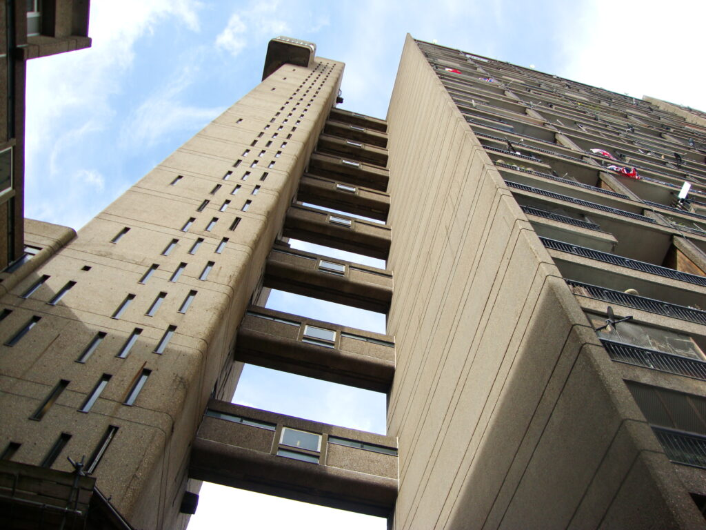 """""""Trellick Tower"""" by Alex JD; photo from below looking upwards at gray-beige building with passageways connecting one side to another."""