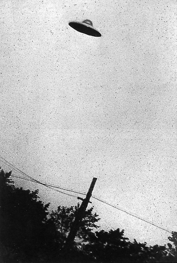 Grainy B&W image of supposed UFO above trees and telephone wires.