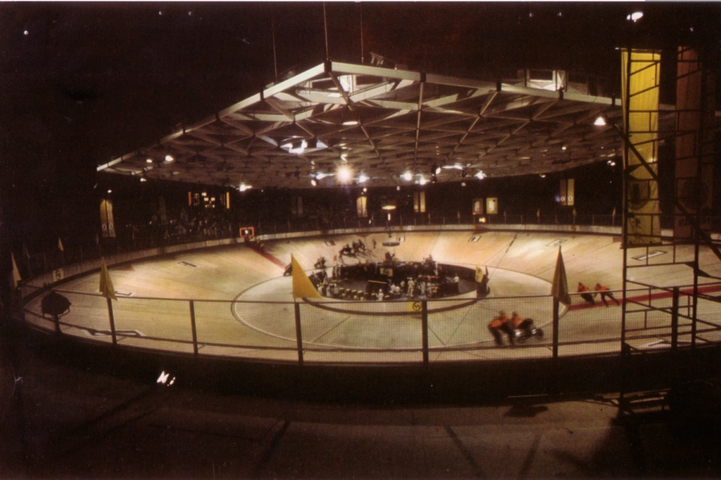 Rollerball's velodrome, a wide rink slanted inward with a metal ceiling and iris in the middle.