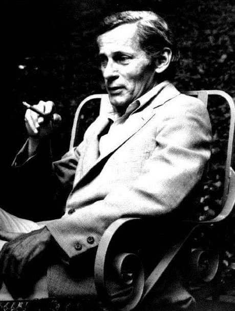 Black and white photo of William Gaddis; Gaddis, in a light-colored suit, reclines against chair with a cigarette in hand and looks away from the camera.