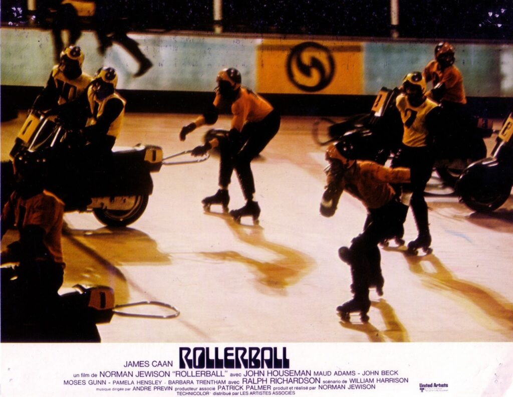Scene from Rollerball; Jonathan E and skaters and motorcyclists in the rink.